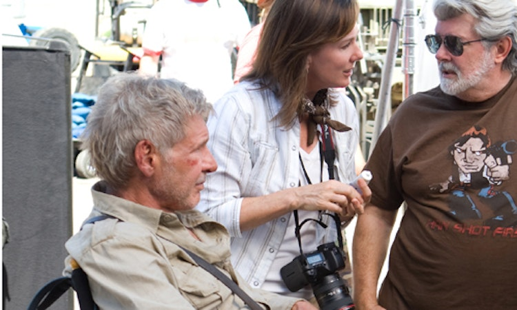 "Harrison Ford, Kathleen Kennedy, and George Lucas. (Note: Lucas is wearing a ""Han Shot First"" fan shirt.)"