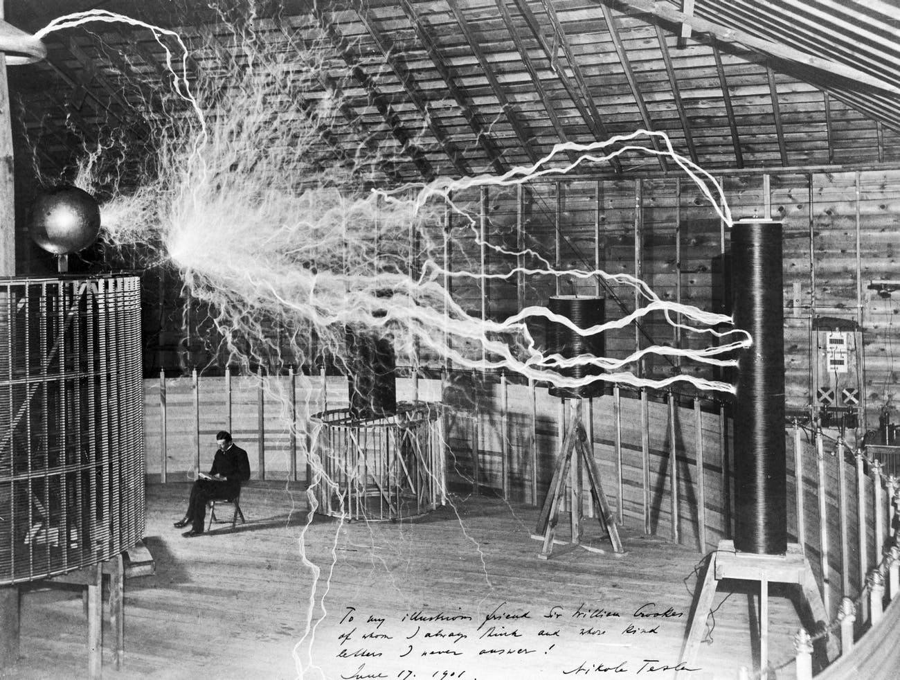 Nikola Tesla sits calmly next to a massive Tesla coil -- or does he? -- in a photo that earned him notoriety