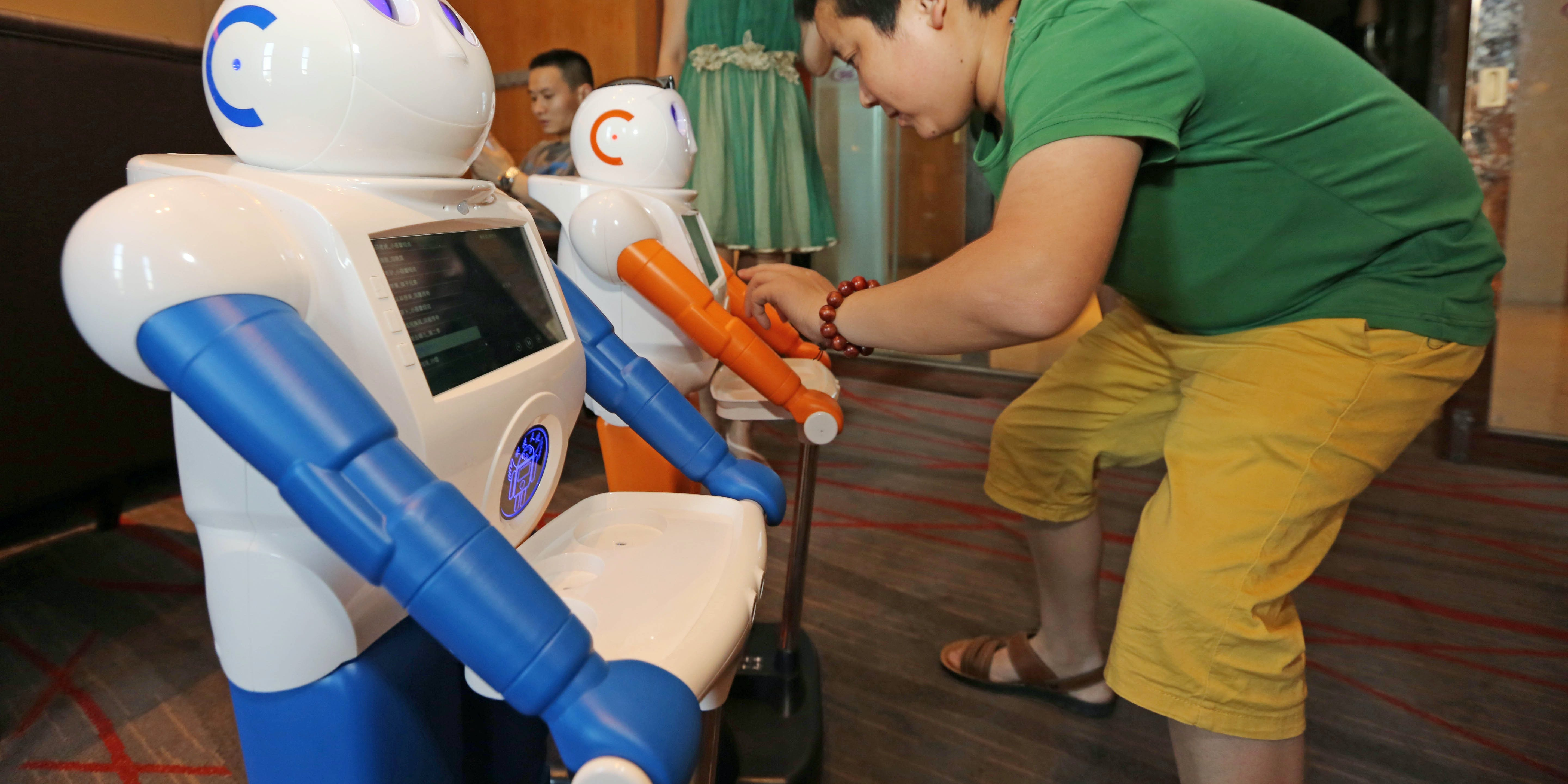 XIANGYANG, CHINA - JUNE 16: (CHINA OUT) A customer touches screen of an artificial intelligent robot at a technological product store on June 16, 2016 in Xiangyang, Hubei Province of China. The robot not only can interact with people but also complete specific assignments according to orders. (Photo by VCG/VCG via Getty Images)