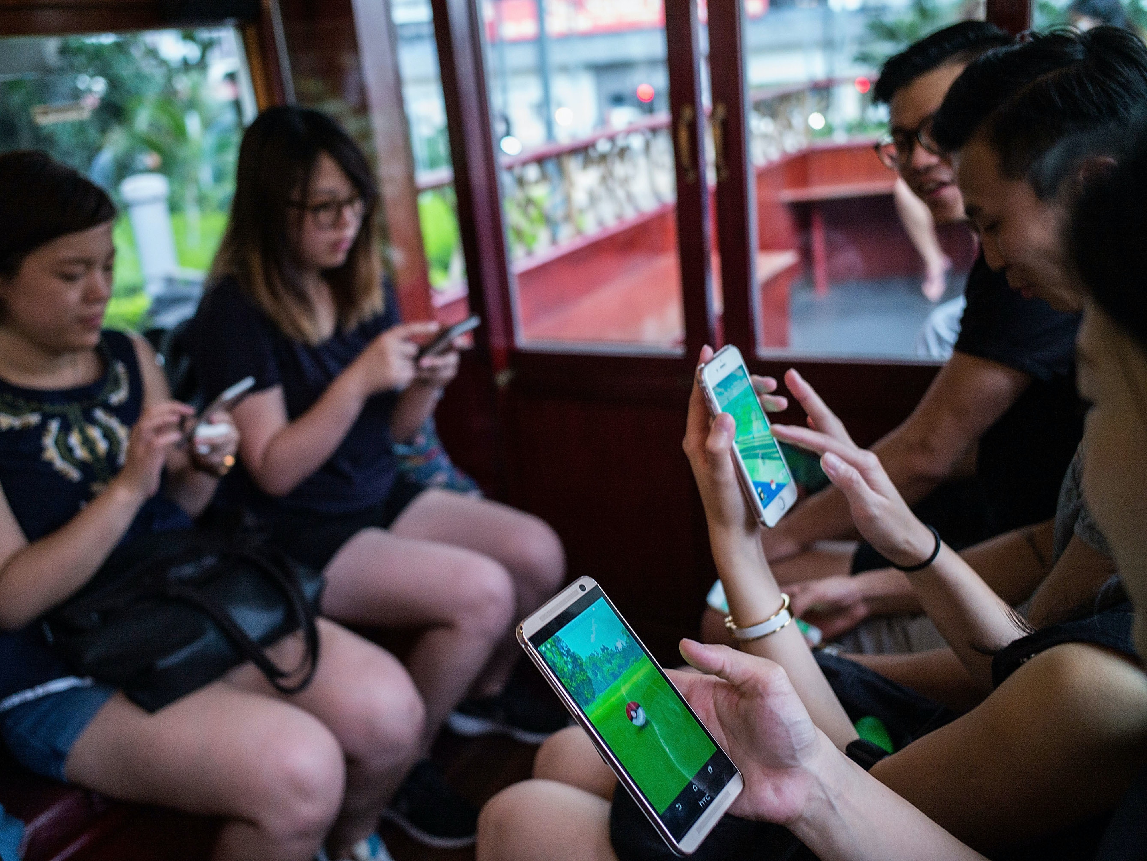 HONG KONG - JULY 30:  People join the Hong Kong's first Pokemon Go tram party organized by 'Sam the Local', on July 30, 2016 in Hong Kong, Hong Kong. Hundreds of youths attended the 18th Ani-Com and Games Hong Kong fair dressed as Japanese comic characters as the reality smartphone game Pokemon GO was launched in Hong Kong this week following the release of the app in Japan. Based on reports, shopping malls and local businesses in Hong Kong are offering Pokemon-related activities to draw in crowds that have flooded the streets to capture Pokemon while authorities aim to ban the game at public hospitals and schools after receiving complaints from the public.  (Photo by Lam Yik Fei/Getty Images)