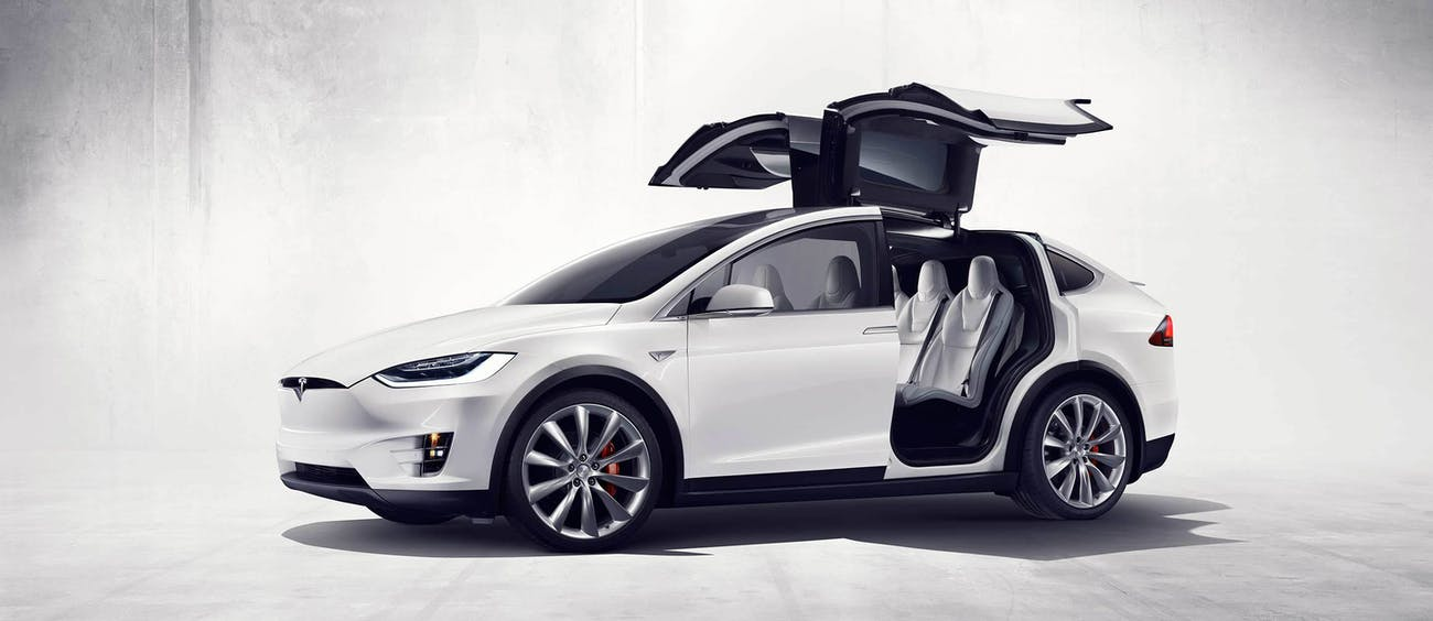 The Tesla Model X with its falcon wing doors open.