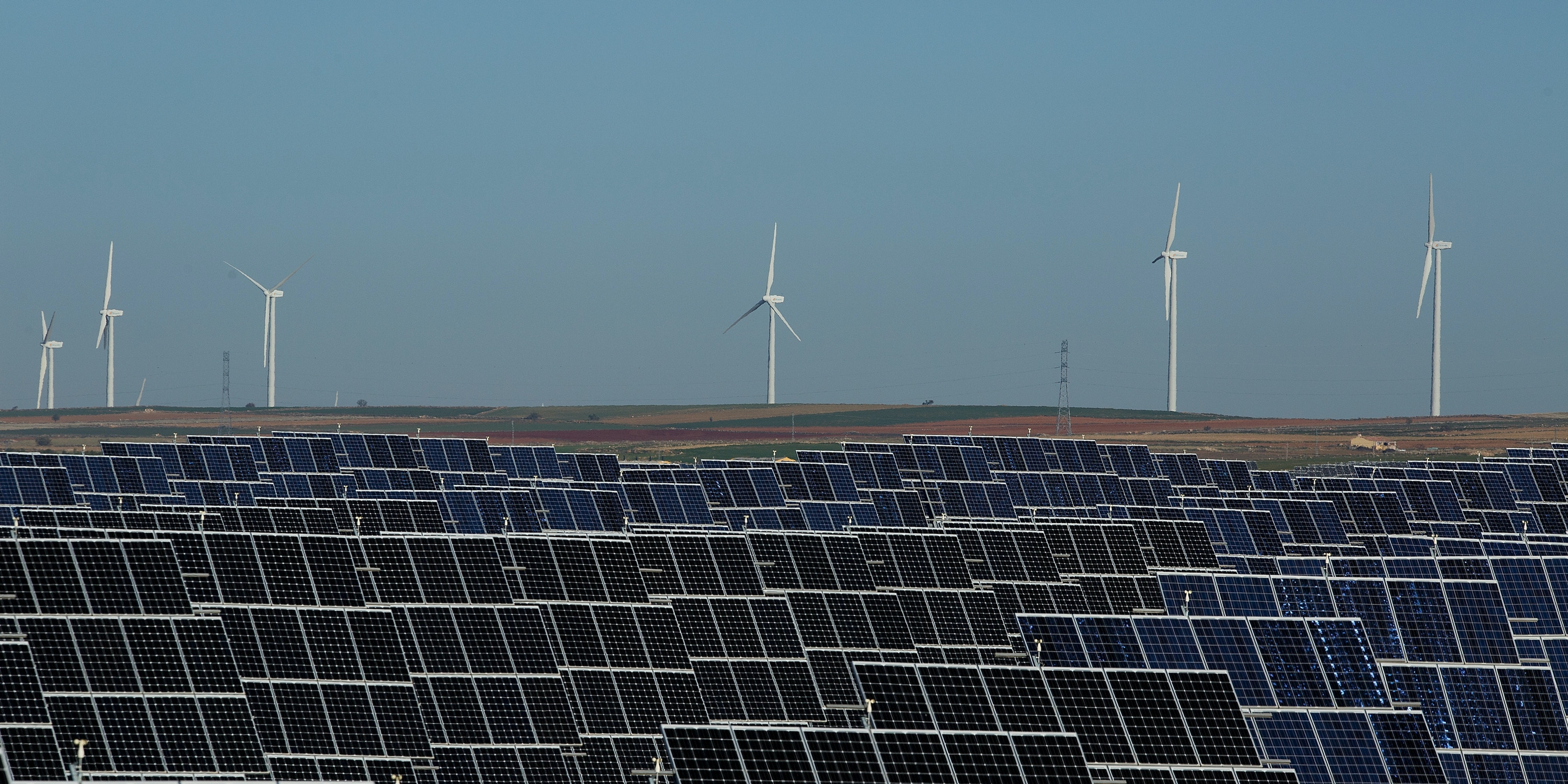 EL BONILLO, SPAIN - DECEMBER 02:  Photovoltaic power panels stand at Abaste's El Bonillo Solar Plant while wind turbines spin at a wind farm on the background on December 2, 2015 in El Bonillo, Albacete province, Spain. Spain in 2008 was a leading country on photovoltaic power and renewable energies but after some law changes the solar power industry collapsed, with companies either closing or turning to overseas markets. The UN Climate Change Summit is taking place in Paris over two weeks, in an attempt to agree on an international deal to curb greenhouse gas emissions.  (Photo by Pablo Blazquez Dominguez/Getty Images)