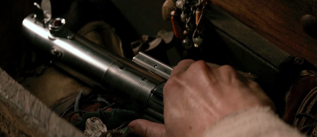 Rey grasping Luke's old lightsaber in 'The Force Awakens.'