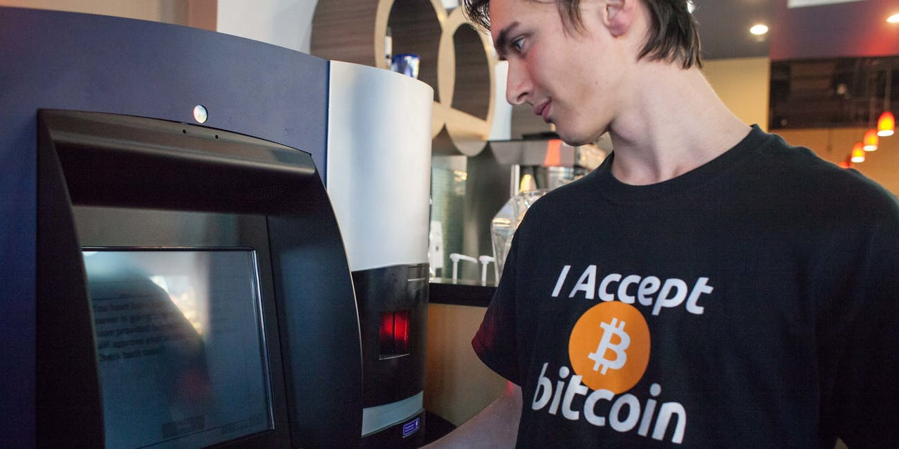 VANCOUVER, BC - OCTOBER 29: Gabriel Scheare uses the world's first bitcoin ATM on October 29, 2013 at Waves Coffee House in Vancouver, British Columbia. Scheare said he 'just felt like being part of history.' The ATM, named Robocoin, allows users to buy or sell the digital currency known as bitcoins. Once only used for black market sales on the internet, bitcoins are starting to be accepted at a growing number of businesses. (Photo by David Ryder/Getty Images)