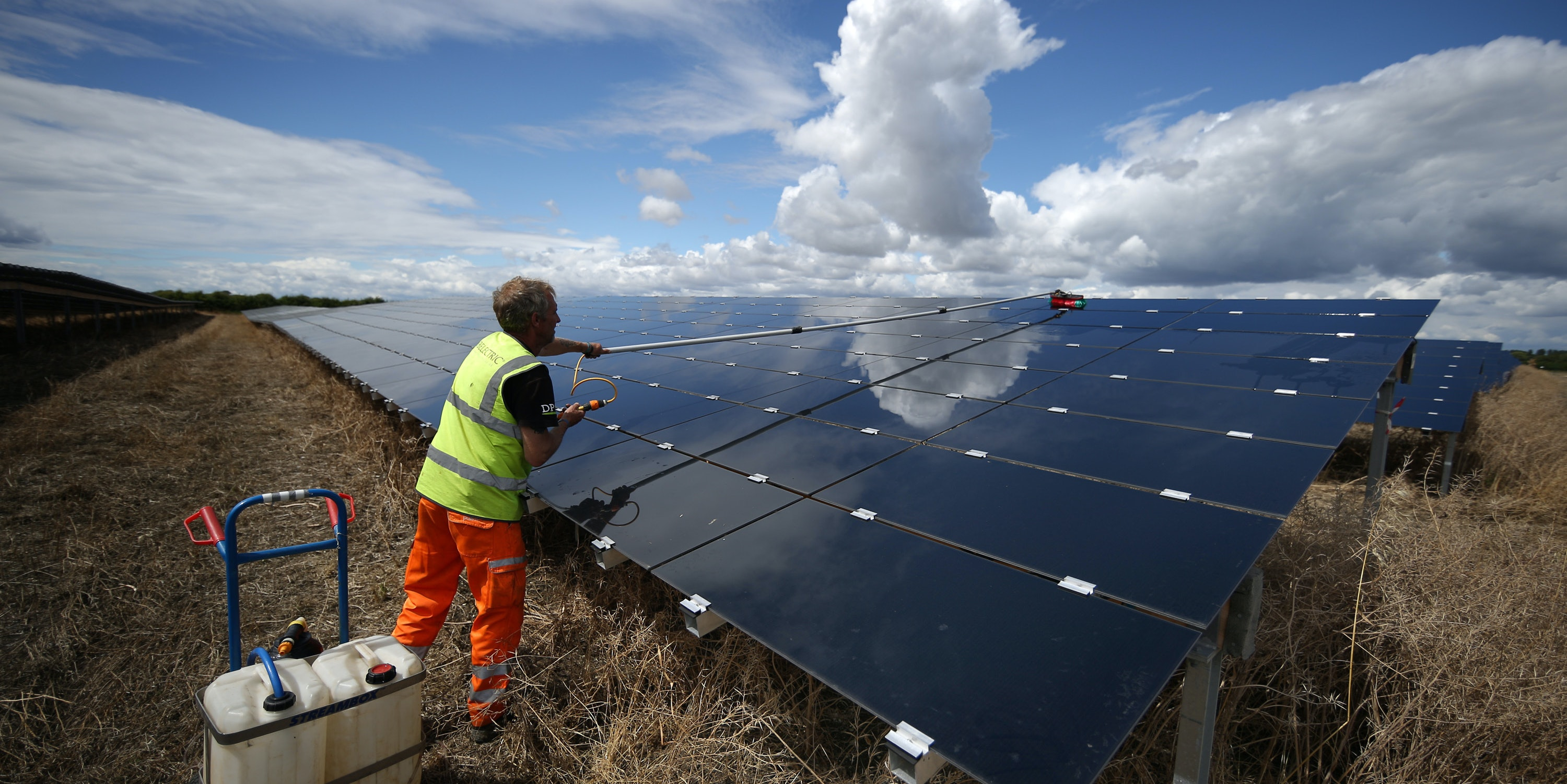 ABINGDON, ENGLAND - JULY 29:  A workman cleans panels at Landmead solar farm on July 29, 2015 near Abingdon, England. The 46 megawatt capacity installation was the largest in the United Kingdom when it was completed in 2014. Operated by BELECTRIC UK it supplies around 45 million kWh (kilowatt hours) of clean energy per year, enough to power 14,000 average homes.  (Photo by Peter Macdiarmid/Getty Images)