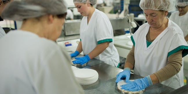Women pack tartas de turron (turron tarts) at the El Abuelo artisan factory on November 24, 2015 in Jijona, Spain.  Turron, a nougat confection of toasted almonds mixed with honey, sugar and egg yolk is produced almost exclusively in Jijona and is popular throughout Spain and Latin America as a traditional christmas dessert. Turron has been produced in Jijona since 1850 when the family-run Primitivo Rovira set up and currently employs 25 workers in total.