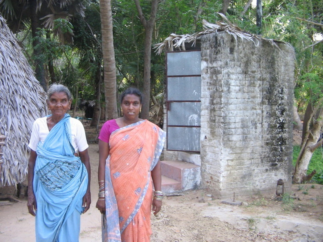 A Tamil woman and her mother-in-law in front of their toilet whose roof caved in - hence the thatch.