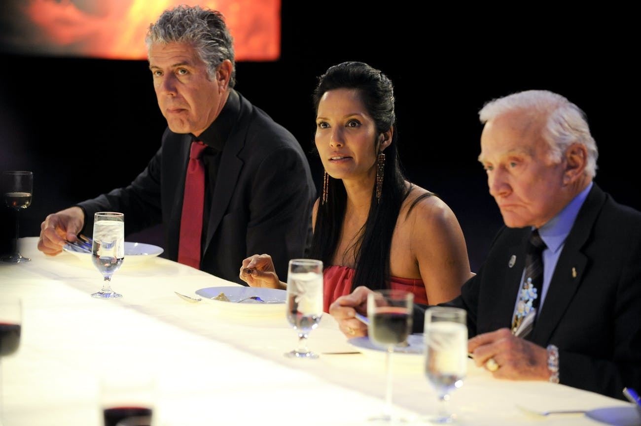 "Anthony Bourdain, Padma Lakshmi, and Buzz Aldrin dining during the ""Space Food"" episode of Top Chef"