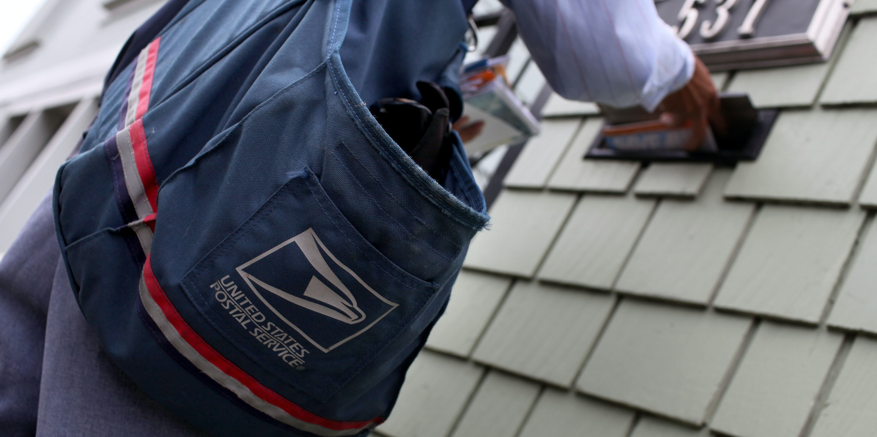 US Postal Service letter carrier Anthony Ow places letters in a mailbox as he walks his delivery route July 30, 2009 in San Francisco, California.