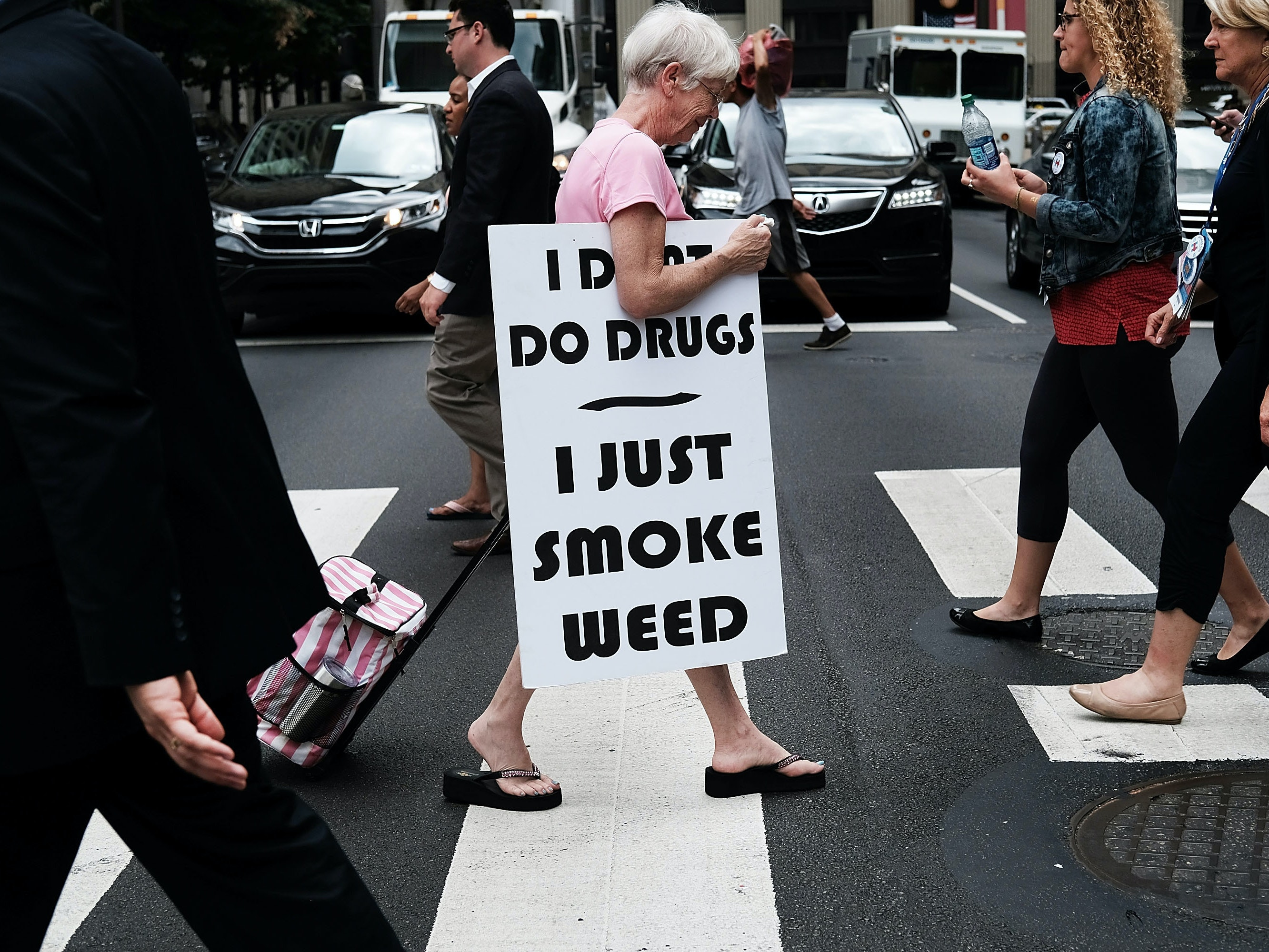 PHILADELPHIA, PA - JULY 28: A woman walks with a sign supporting legalizing marijuana during the Democratic National Convention (DNC) on July 28, 2016 in Philadelphia, Pennsylvania. The convention officially began on Monday and has attracted thousands of protesters, members of the media and Democratic delegates to the City of Brotherly Love.  (Photo by Spencer Platt/Getty Images)