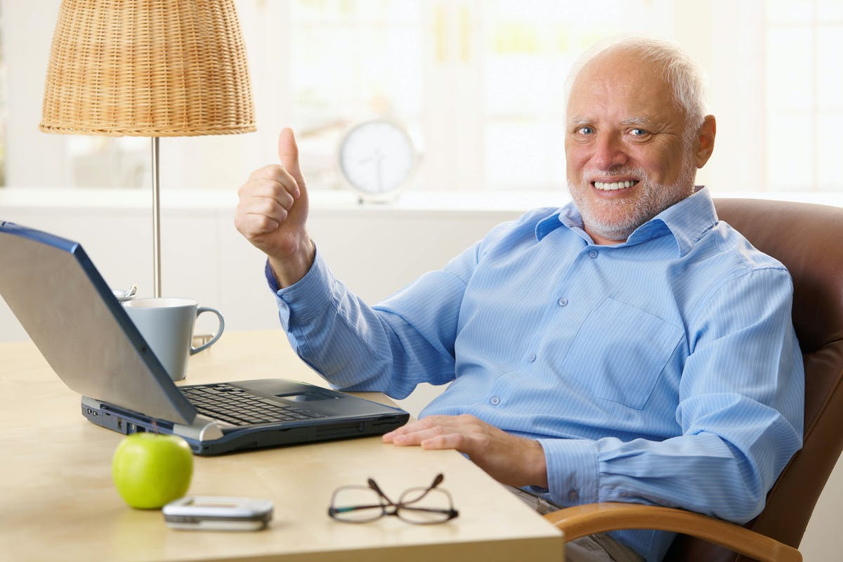 Old man gives thumbs up with laptop