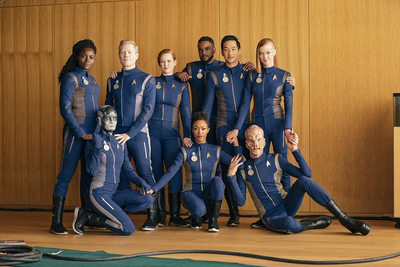From left to right: Oyin Oladejo as Joann Owosekun; Sara Mitich as Airiam; Anthony Rapp as Paul Stamets; Mary Wiseman as Sylvia Tilly; Sonequa Martin-Green as Michael Burnham; Ronnie Rowe as Bryce; Patrick Kwok-Choon as Rhys; Doug Jones as Saru; Emily Coutts as Keyla Detmer