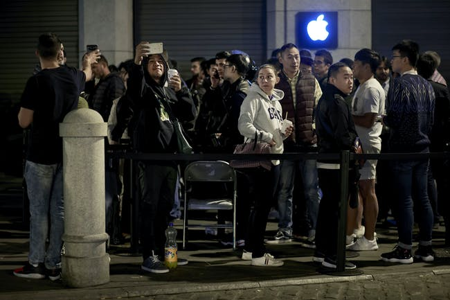 Customers take pictures with their mobile phones as they queue at Puerta del Sol Apple Store before its opening the day the company launches their iPhone 7 and 7 Plus on September 16, 2016 in Madrid, Spain.