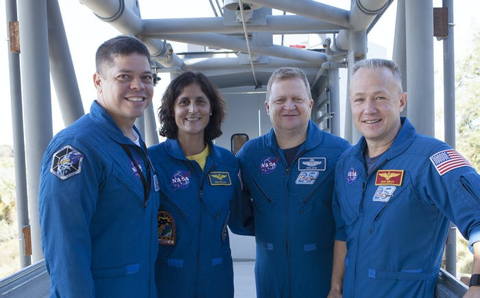 Commercial Crew astronauts, left to right, Bob Behnken, Suni Williams, Eric Boe, and Doug Hurley stand on the Crew Access Arm leading to the White Room at a construction yard near NASA's Kennedy Space Center in Florida.