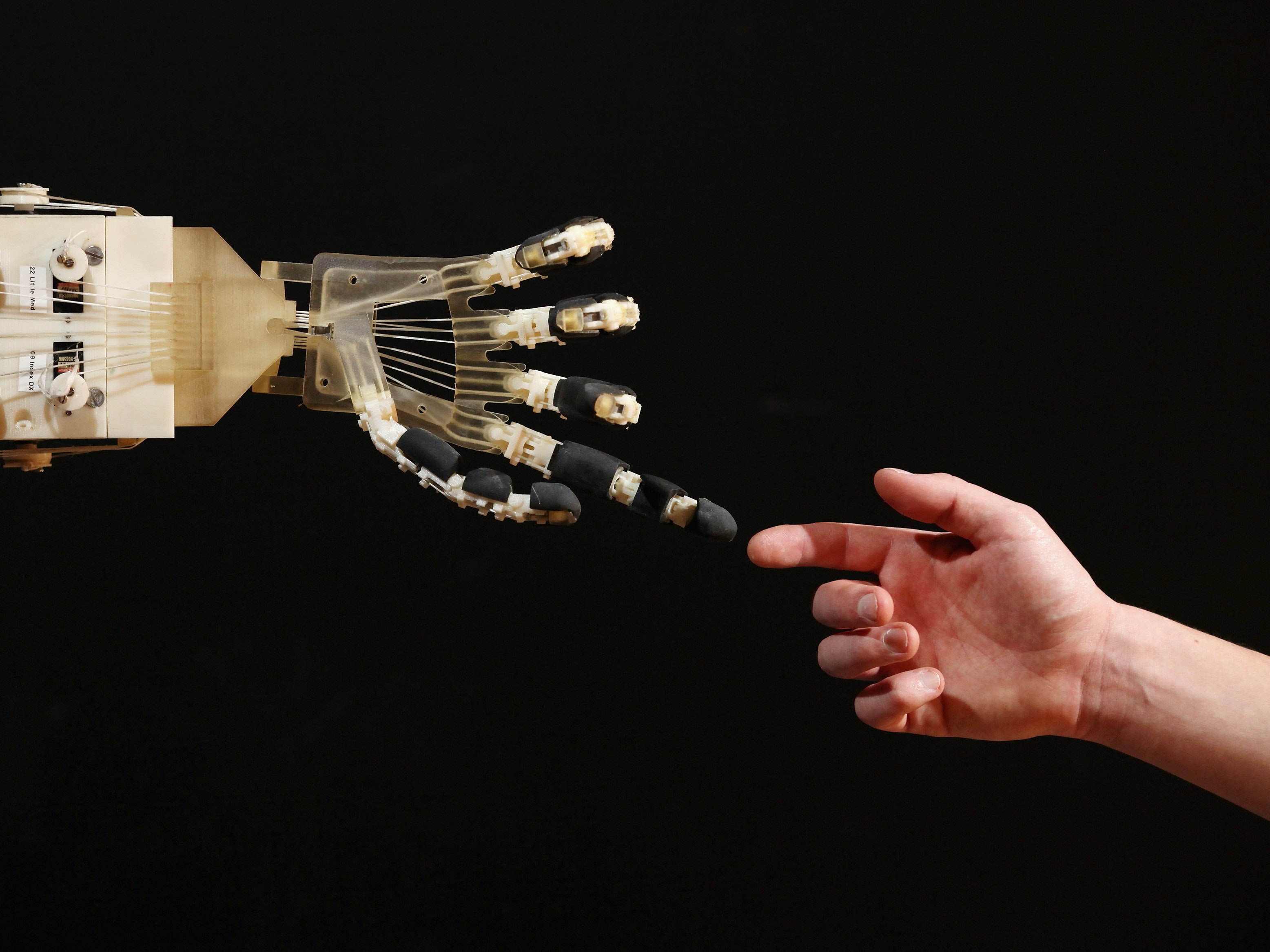 Robotics student Gildo Andreoni interacts with a Dexmart robotic hand built at the University of Bologna in the Robotville exhibition at the Science Museum on November 29, 2011 in London, England. The Science Museum's Robotville exhibition showcases 20 unique and cutting-edge robots from European research laboratories, it  is free to enter and runs from December 1-4, 2011.