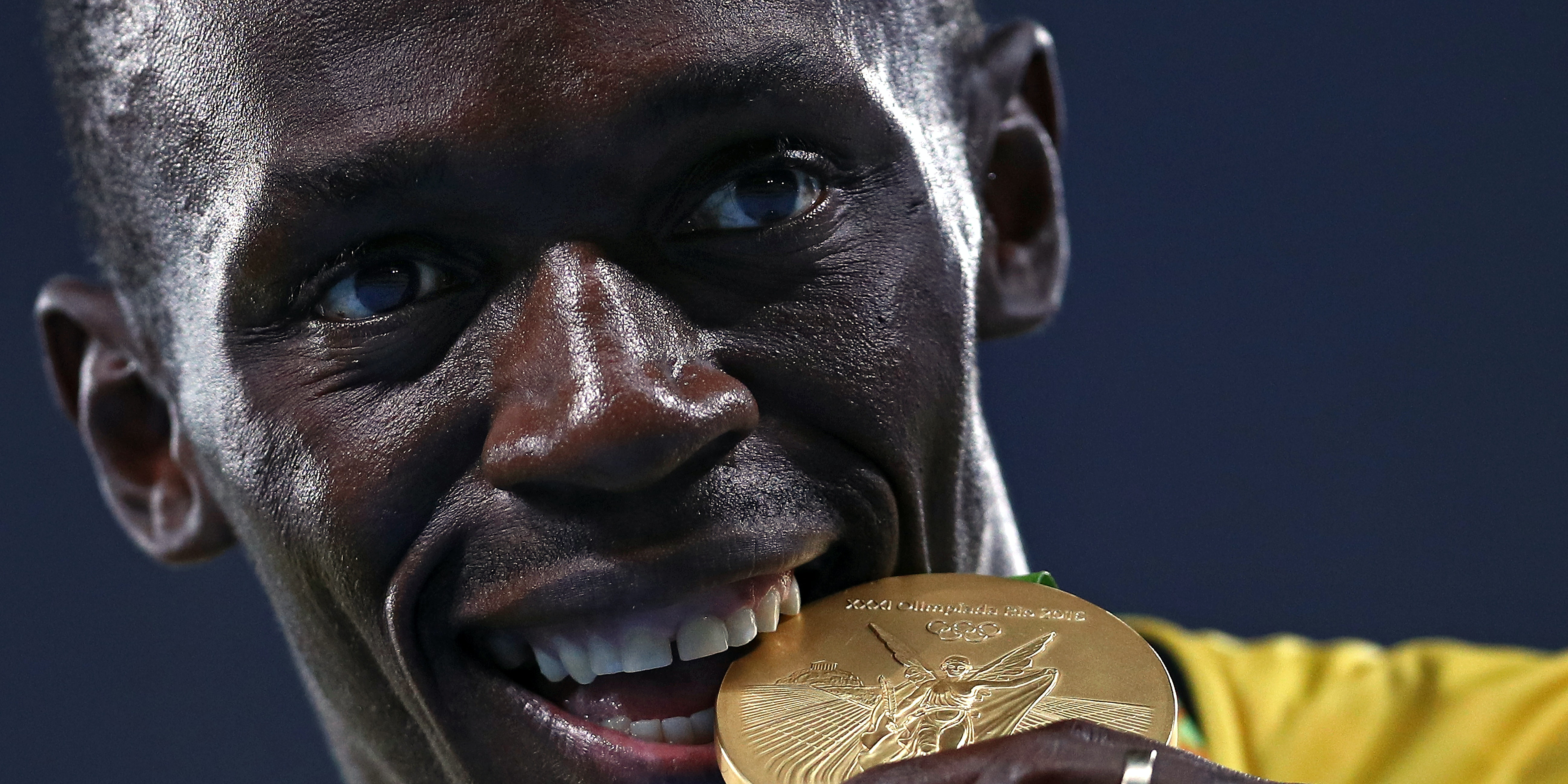 RIO DE JANEIRO, BRAZIL - AUGUST 20:  Gold medalist Usain Bolt of Jamaica bites his gold medal during the medal ceremony for the Men's 4 x 100 meter Relay on Day 15 of the Rio 2016 Olympic Games at the Olympic Stadium on August 20, 2016 in Rio de Janeiro, Brazil. (Photo by Patrick Smith/Getty Images)
