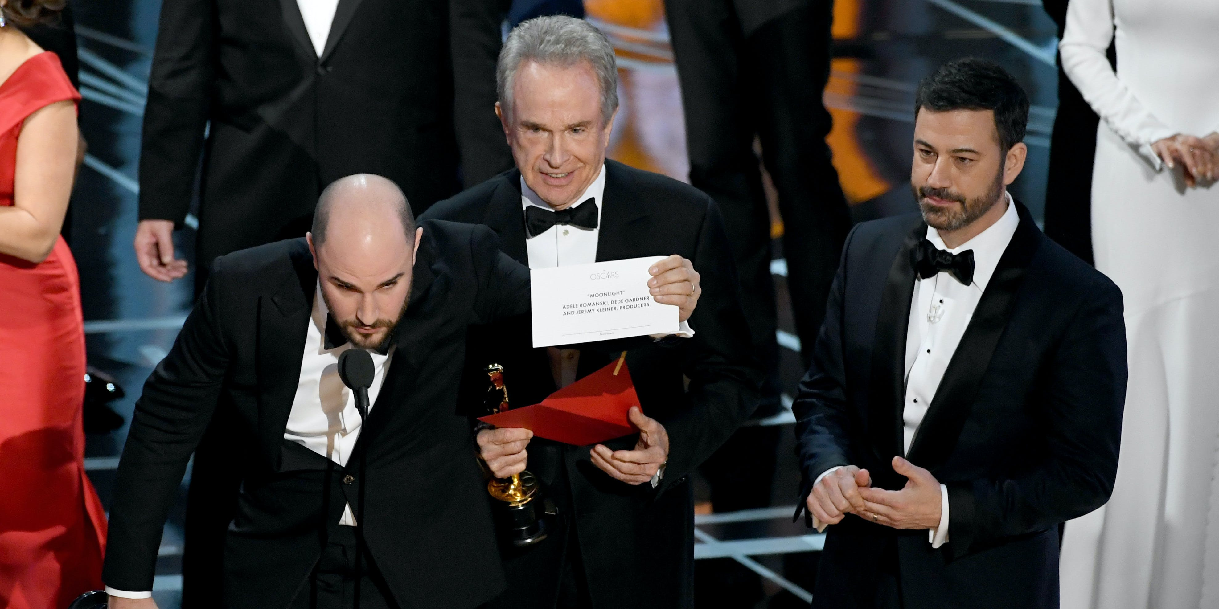 HOLLYWOOD, CA - FEBRUARY 26:  'La La Land' producer Jordan Horowitz holds up the winner card reading actual Best Picture winner 'Moonlight' with actor Warren Beatty and host Jimmy Kimmel onstage during the 89th Annual Academy Awards at Hollywood & Highland Center on February 26, 2017 in Hollywood, California.  (Photo by Kevin Winter/Getty Images)