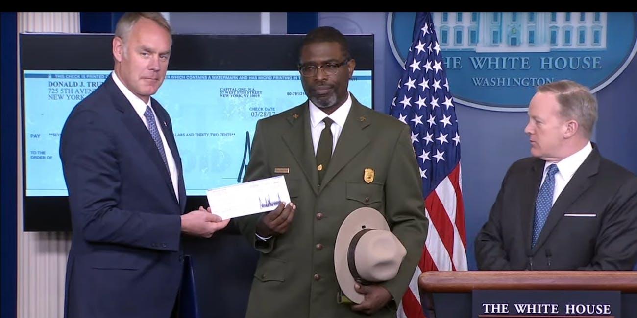 White House Press Secretary Sean Spicer began his press briefing by handing a check to Secretary of the Interior Ryan Zinke.
