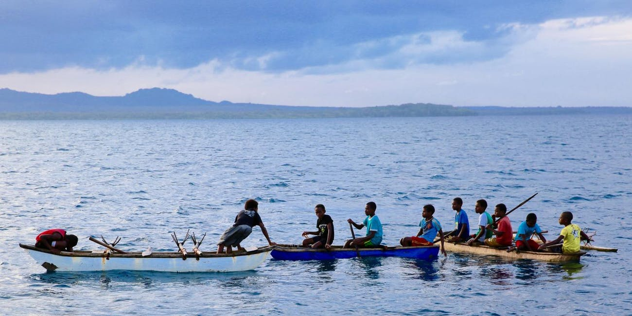 Young men in canoes in Northwest Malakula, Vanuatu.