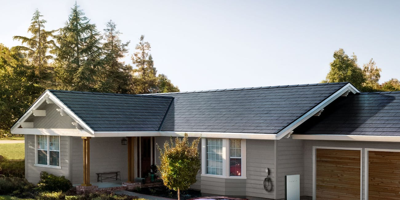 Tesla Solar Roof V3 with a Tesla Model 3 in the driveway.