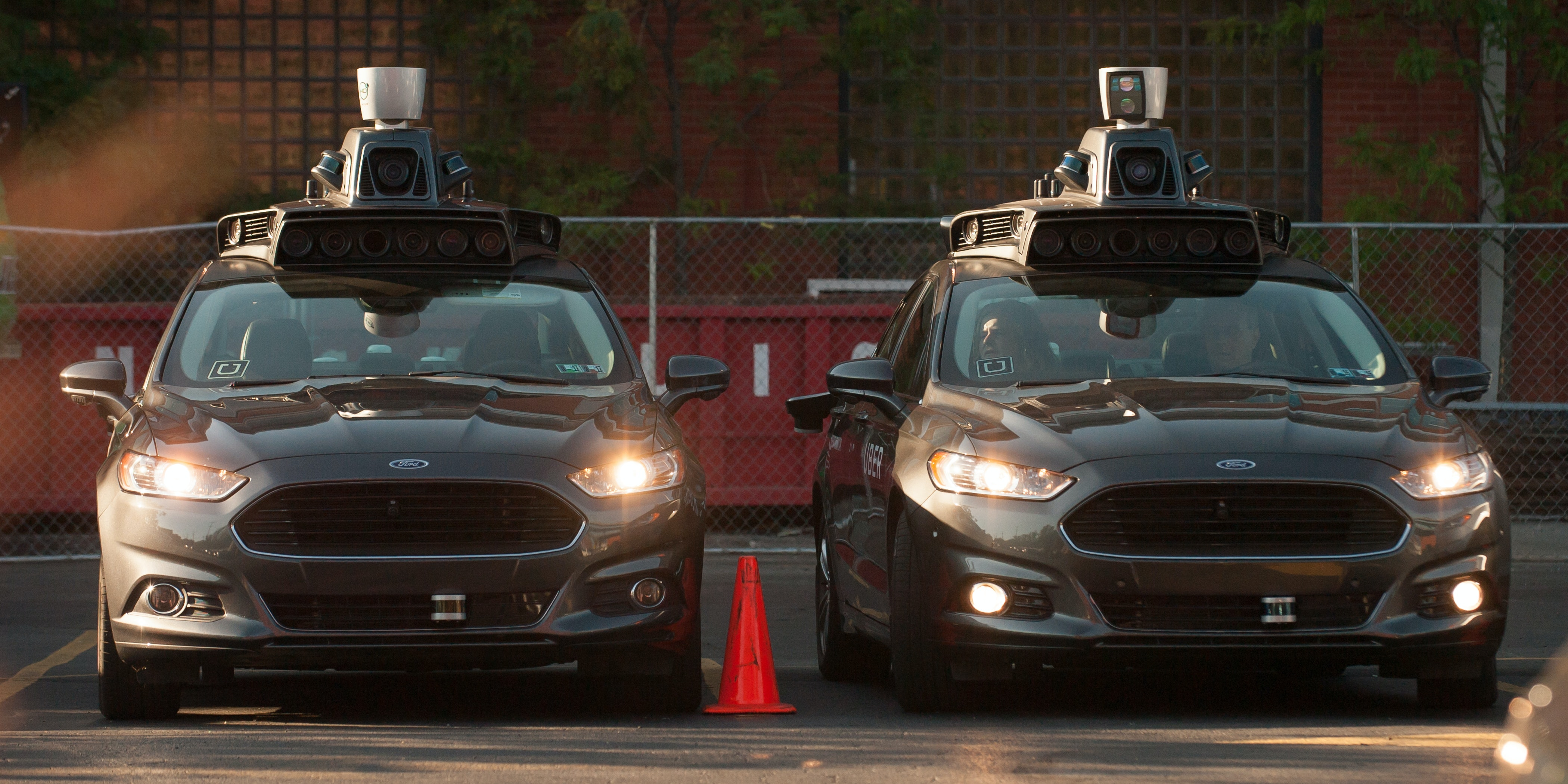 Uber driverless Ford Fusions sit in the Uber Technical Center parking lot with their lights on for some reason.