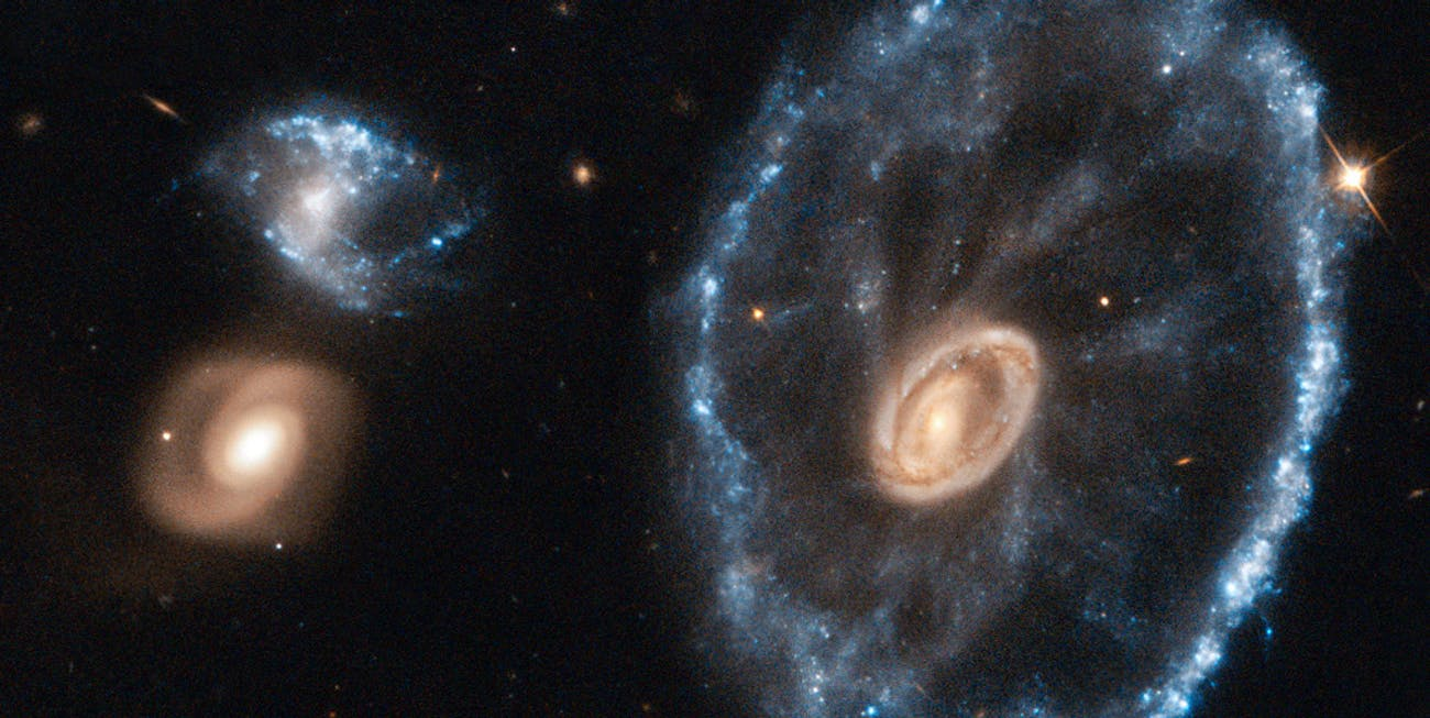 The Cartwheel Galaxy next to two smaller galaxies.