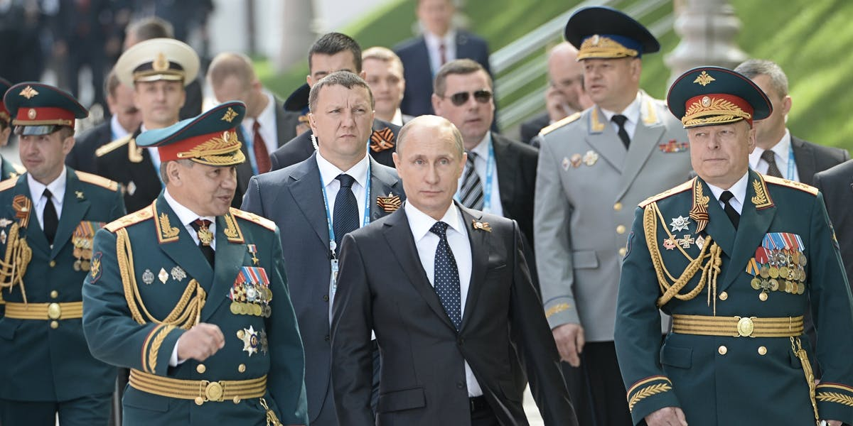 In this handout image supplied by Host photo agency / RIA Novosti, Russian President Vladimir Putin, center, Russian Defense Minister and Army General Sergei Shoigu, left, and Victory Parade Commander and Commander-in-Chief of the Russian Ground Forces, Colonel-General Oleg Salyukov, right, before the flower-laying ceremony at the Tomb of the Unknown Soldier.