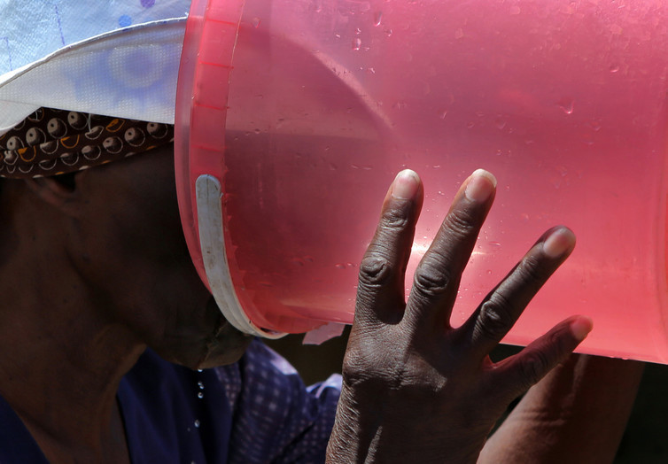An elderly woman drinking water after waiting hours in line for it in January 2016 in South Africa.