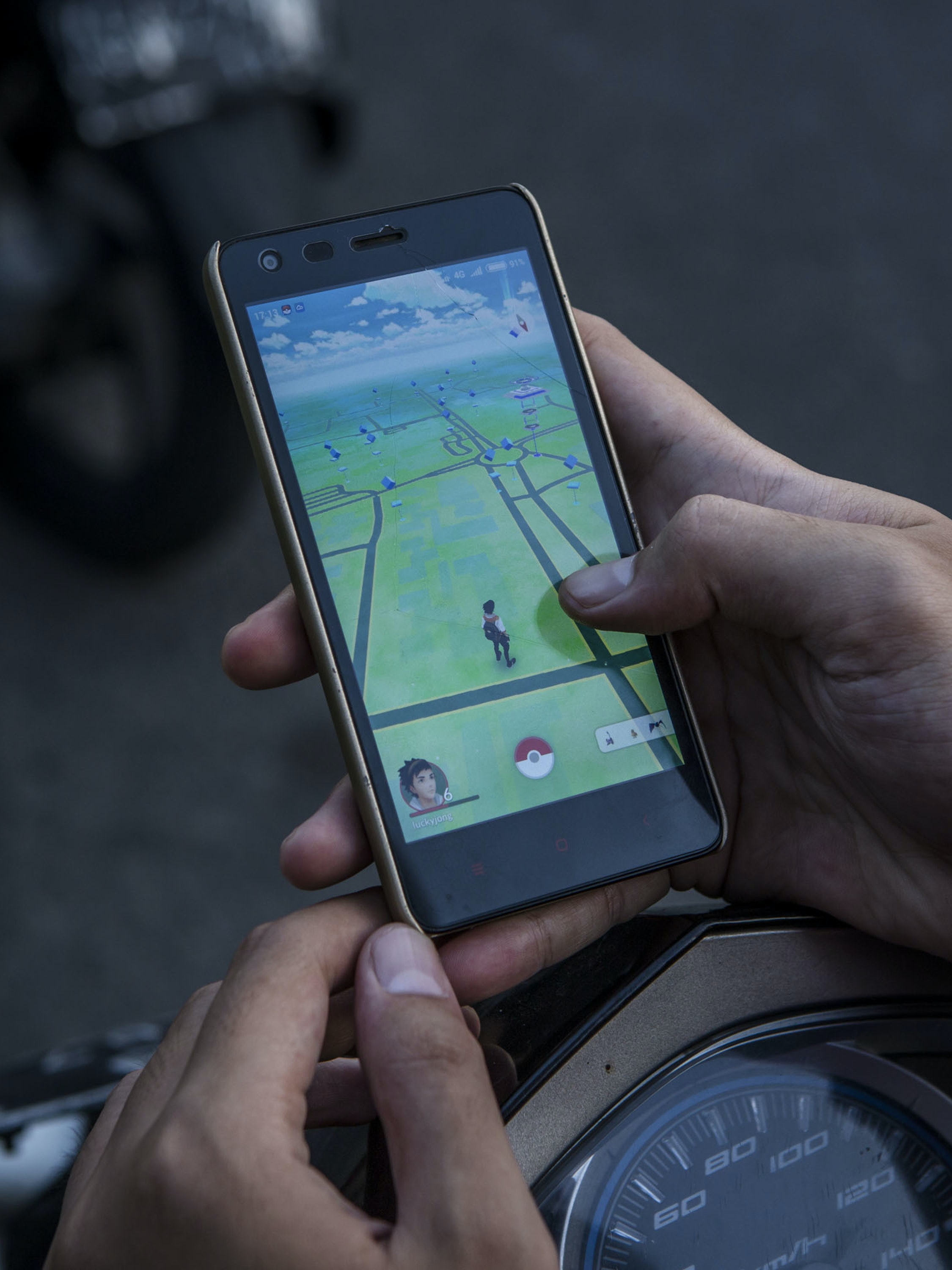 YOGYAKARTA, INDONESIA - JULY 24:  A motorcyclist, plays Pokemon Go game on his smartphone on July 24, 2016 in Yogyakarta, Indonesia. 'Pokemon Go,' which uses Google Maps and a smartphone has been a smash-hit in countries where it is available and already popular in Indonesia even though it has not been officially released. Indonesians have been downloading the game by using a proxy location which gives them access to app stores of other countries as security officials have voiced worries that the game could pose a security threat.  (Photo by Ulet Ifansasti/Getty Images)