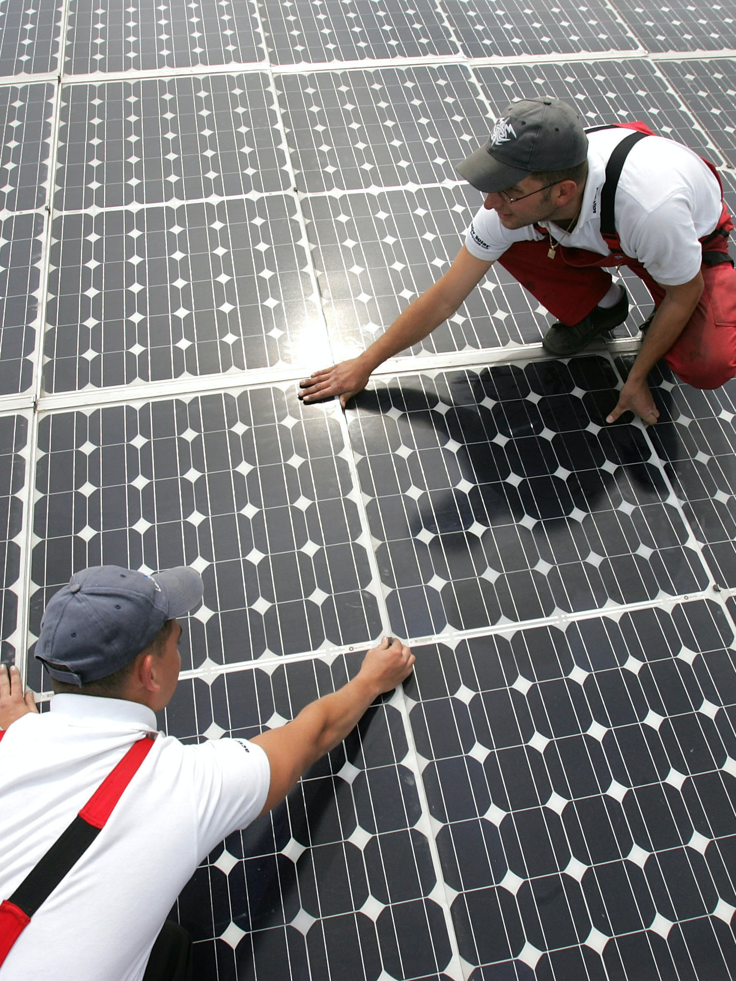 BUERSTADT, GERMANY - MAY 13: Two workers maintain solar panels on the roof of a warehouse on May 13, 2005 in Buerstadt, Germany. The 50,000 square meter system with a capacity of 4,5 megawatts per year represents the largest roof based solar system worldwide.  (Photo by Ralph Orlowski/Getty Images) *** Local Caption ***