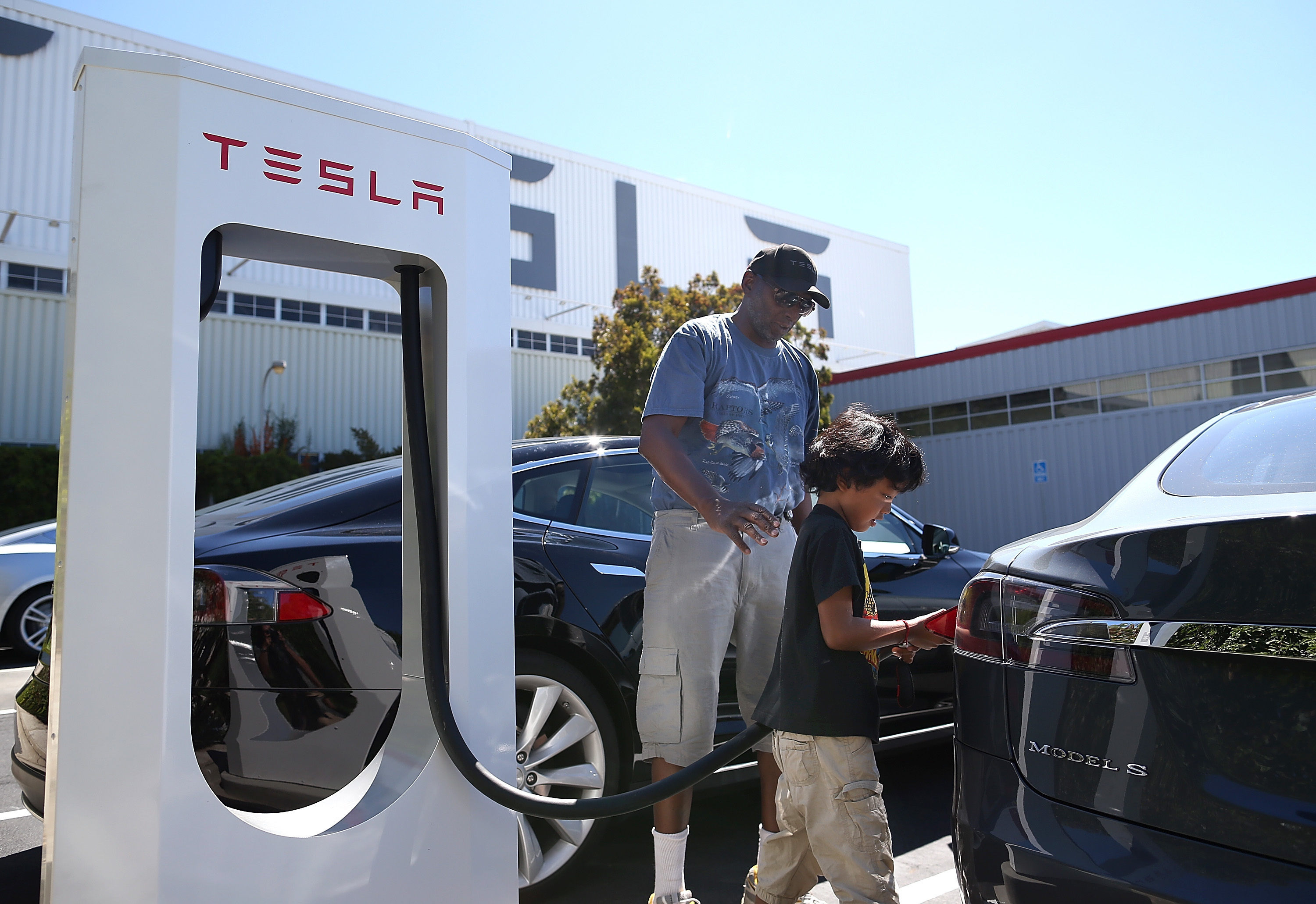 Jinyao Desandies (R) and Dandre Desandies (L) plug the Tesla Supercharger into their Tesla Model S sedan in Fremont, California back in 2013. Then, the supercharger network only had 18 stations nationwide. Now, it has 734.