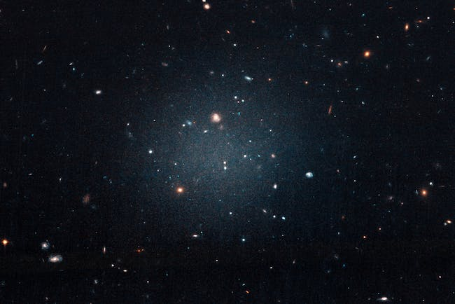 "This large, fuzzy-looking galaxy is so diffuse that astronomers call it a ""see-through"" galaxy because they can clearly see distant galaxies behind it. The ghostly object, catalogued as NGC 1052-DF2, doesn't have a noticeable central region, or even spiral arms and a disk, typical features of a spiral galaxy. But it doesn't look like an elliptical galaxy, either. Even its globular clusters are oddballs: they are twice as large as typical stellar groupings seen in other galaxies. All of these oddities pale in comparison to the weirdest aspect of this galaxy: NGC 1052-DF2 is missing most, if not all, of its dark matter."