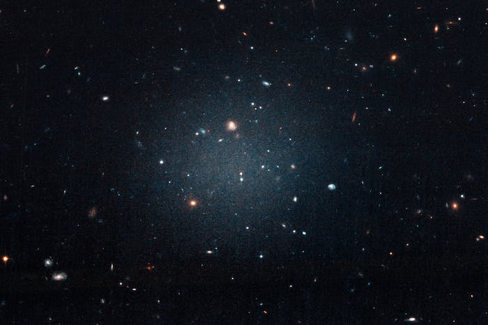 """This large, fuzzy-looking galaxy is so diffuse that astronomers call it a """"see-through"""" galaxy because they can clearly see distant galaxies behind it. The ghostly object, catalogued as NGC 1052-DF2, doesn't have a noticeable central region, or even spiral arms and a disk, typical features of a spiral galaxy. But it doesn't look like an elliptical galaxy, either. Even its globular clusters are oddballs: they are twice as large as typical stellar groupings seen in other galaxies. All of these oddities pale in comparison to the weirdest aspect of this galaxy: NGC 1052-DF2 is missing most, if not all, of its dark matter."""
