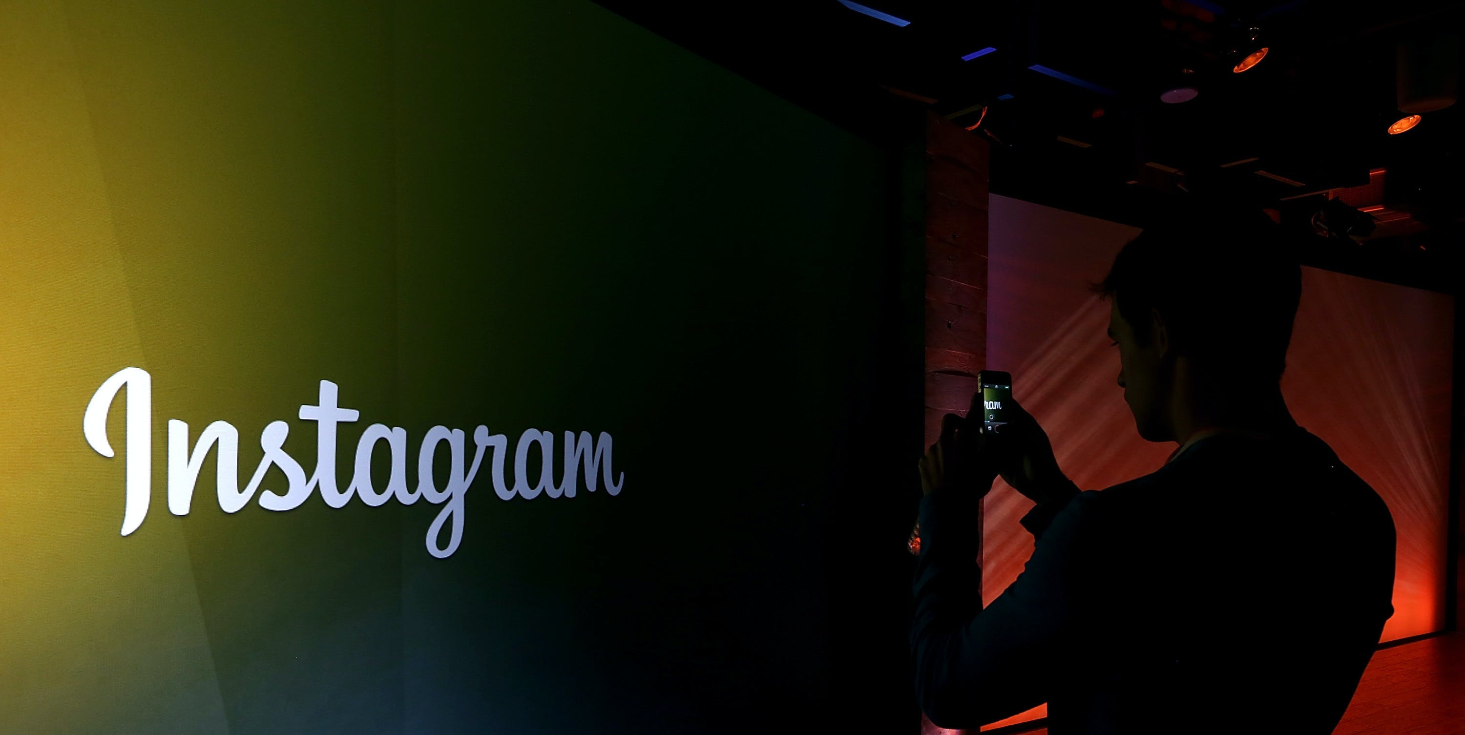 MENLO PARK, CA - JUNE 20:  An attendee takes a photo of the instagram logo during a press event at Facebook headquarters on June 20, 2013 in Menlo Park, California. Facebook announced that its photo-sharing subsidiary Instagram will now allow users to take and share video.  (Photo by Justin Sullivan/Getty Images)