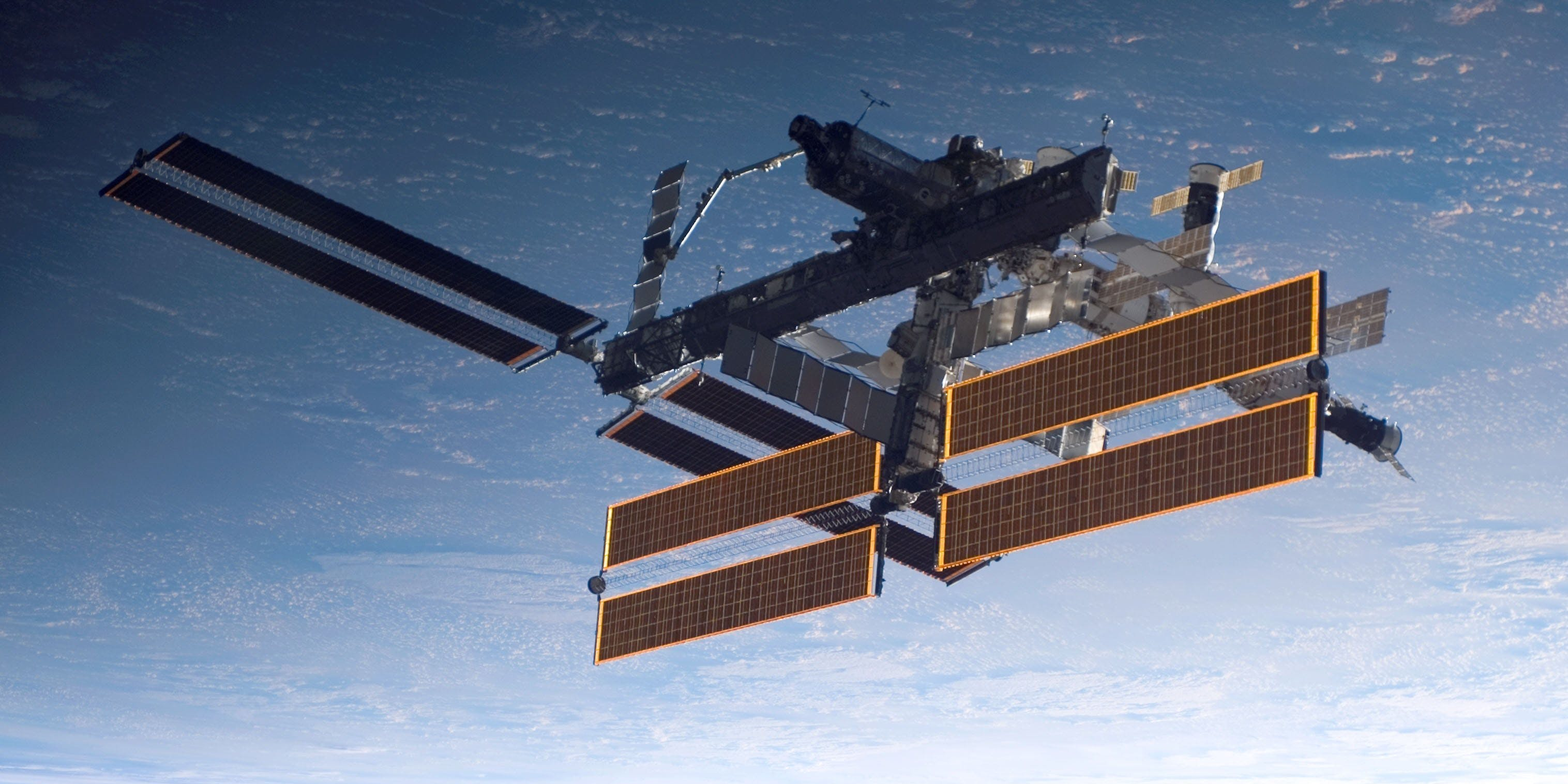 IN SPACE - SEPTEMBER 17: In this handout photo provided by NASA, the International Space Station is seen over a blue and white Earth, taken shortly after the Space Shuttle Atlantis undocked from the orbital outpost at 7:50 a.m. CDT. The unlinking completed six days, two hours and two minutes of joint operations with the station crew. Atlantis left the station with a new, second pair of 240-foot solar wings, attached to a new 17.5-ton section of truss with batteries, electronics and a giant rotating joint. The new solar arrays eventually will double the station's onboard power when their electrical systems are brought online during the next shuttle flight, planned for launch in December.  (Photo by NASA via Getty Images)
